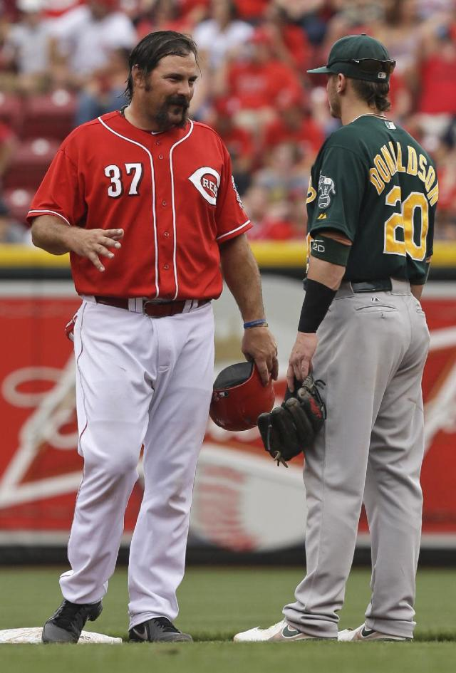 Cincinnati Reds' Corky Miller (37) talks with Oakland Athletics third baseman Josh Donaldson at second base in the third inning of a baseball game, Wednesday, Aug. 7, 2013, in Cincinnati. Miller had just hit a double to drive in a run. (AP Photo/Al Behrman)