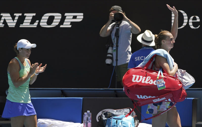 Australia's Ashleigh Barty, left, applauds as Petra Kvitova of the Czech Republic leaves Rod Laver Arena following their quarterfinal match at the Australian Open tennis championship in Melbourne, Australia, Tuesday, Jan. 28, 2020. (AP Photo/Lee Jin-man)