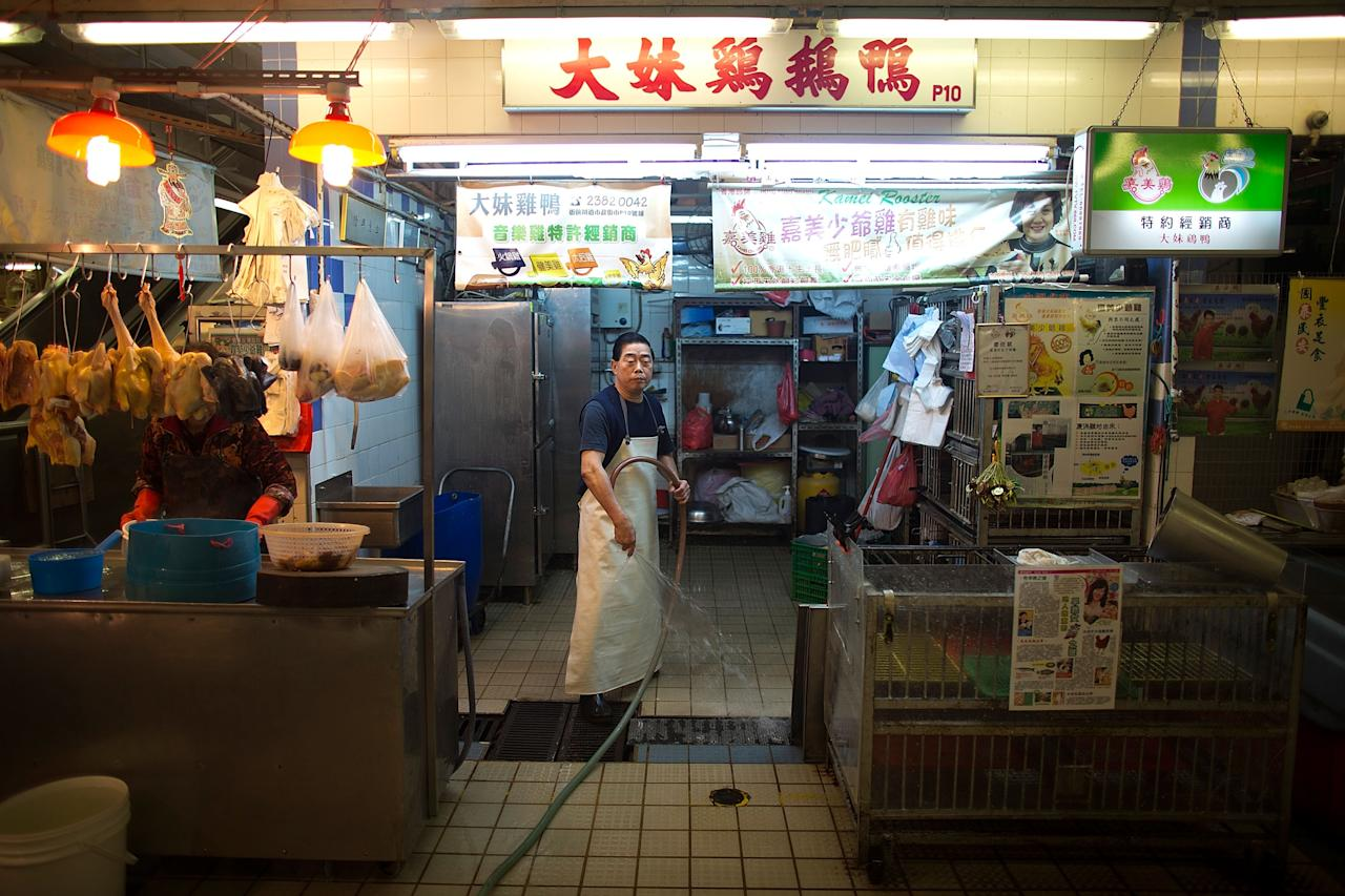 HONG KONG - APRIL 12:  A vendor washes empty chicken cages at the Kowloon City Market on April 12, 2013 in Hong Kong. Local authorities have stepped up the testing of live poultry imports from China to include a rapid test for the H7N9 'bird flu' virus. Measures were put in place as the tenth victim of the influenza strain was confirmed in mainland China yesterday.  (Photo by Lam Yik Fei/Getty Images)