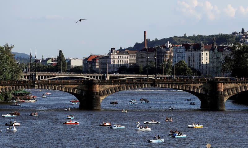 FILE PHOTO: People ride pedal boats on the Vltava river in Prague
