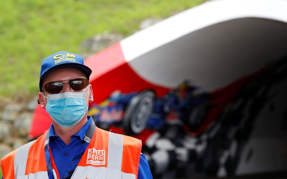 Formula One F1 - Austrian Grand Prix - Red Bull Ring, Spielberg, Styria, Austria - July 2, 2020 A member of the Austrian Grand Prix security is pictured wearing a protective face mask ahead of the Austrian Grand Prix, as F1 resumes following the outbreak of the coronavirus disease - REUTERS/Leonhard Foeger