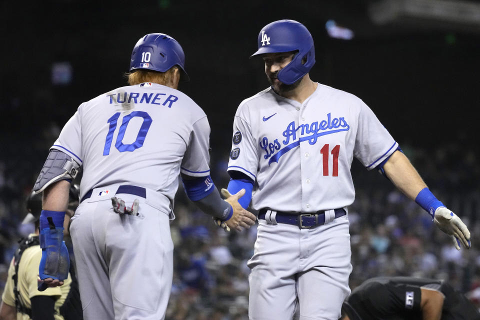 Los Angeles Dodgers' AJ Pollock celebrates with Justin Turner (10) after hitting a two-run home run against the Arizona Diamondbacks in the second inning during a baseball game, Friday, Sept. 24, 2021, in Phoenix. (AP Photo/Rick Scuteri)