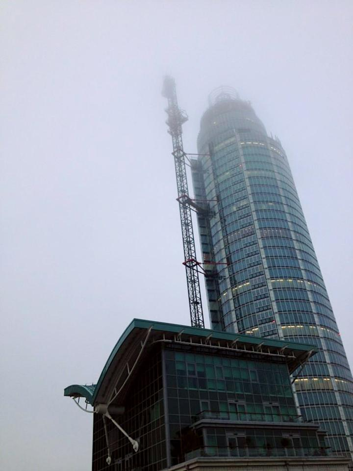 LONDON, UNITED KINGDOM - JANUARY 16: (BEST QUALITY AVAILABLE)  Mist shrowds St Georges Wharf Tower after  a nearby helicopter crash on January 16, 2012 in London, England.  The helicopter appeared to hit a crane attached to the nearby St Georges Wharf Tower before plunging  into the road below during the morning rush hour.   (Photo by Victor Jimenez/Getty Images)