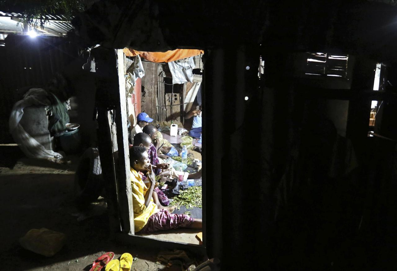 """Somali men sit and chew khat inside a makeshift building at night in Mogadishu August 6, 2014. Grown on plantations in the highlands of Kenya and Ethiopia, tonnes of khat, or qat, dubbed """"the flower of paradise"""" by its users, are flown daily into Mogadishu airport, to be distributed from there in convoys of lorries to markets across Somalia. Britain, whose large ethnic Somali community sustained a lucrative demand for the leaves, banned khat from July as an illegal drug. This prohibition jolted the khat market, creating a supply glut in Somalia and pushing down prices, to the delight of the many connoisseurs of its amphetamine-like high. Picture taken August 6, 2014. REUTERS/Feisal Omar (SOMALIA - Tags: AGRICULTURE DRUGS SOCIETY BUSINESS CRIME LAW)  ATTENTION EDITORS: PICTURE 16 OF 16 FOR WIDER IMAGE PACKAGE 'KHAT - SOMALIA'S PARADISE FLOWER'  TO FIND ALL IMAGES SEARCH 'KHAT OMAR'"""