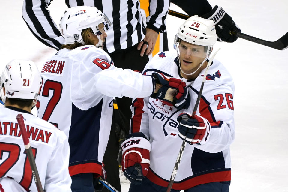 Washington Capitals' Nic Dowd (26) celebrates his goal with Carl Hagelin (62) during the first period of an NHL hockey game against the Pittsburgh Penguins in Pittsburgh, Sunday, Jan. 17, 2021. (AP Photo/Gene J. Puskar)