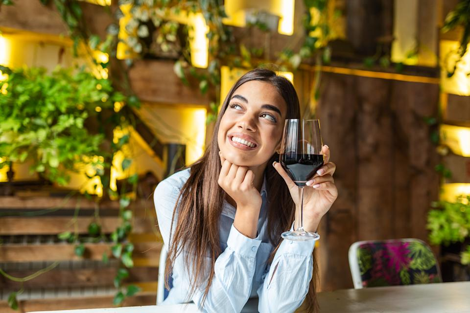 Image of cute pretty young woman sitting in cafe holding glass and drinking wine. portrait of a beautiful wine tasting tourist woman.