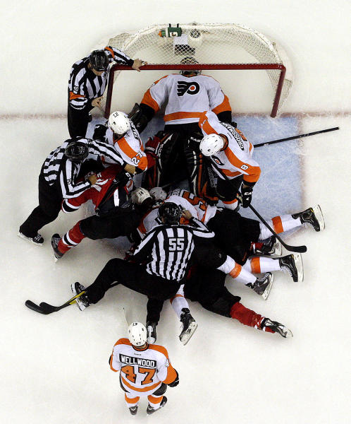 Philadelphia Flyers goalie Ilya Bryzgalov, of Russia, lays on his back after making a save as a group of players are pulled apart by officials during Game 4 of a second-round NHL hockey Stanley Cup playoff series against the New Jersey Devils, Sunday, May 6, 2012 in Newark, N.J. The Devils won 4-2 and take a 3-1 lead in the series. (AP Photo/Julio Cortez)