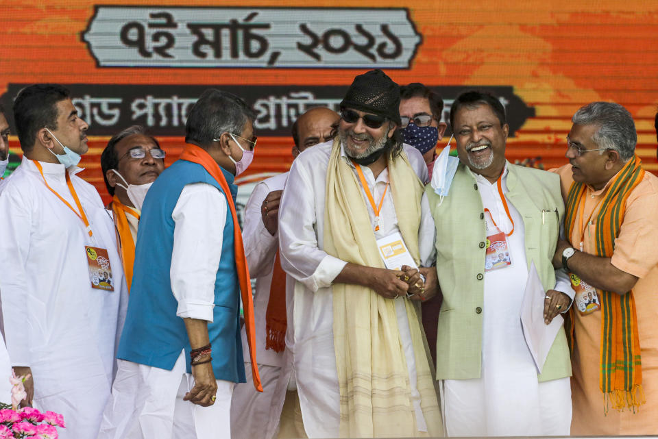 Bollywood actor Mithun Chakrabarty, third right, is greeted on dais by Bharatiya Janata Party leaders, Dilip Ghosh, right, Mukul Roy, second right and Suvendu Adhikari, left prior to joining the party ahead of West Bengal state elections in Kolkata, India, Sunday, March 7, 2021. (AP Photo/Bikas Das)