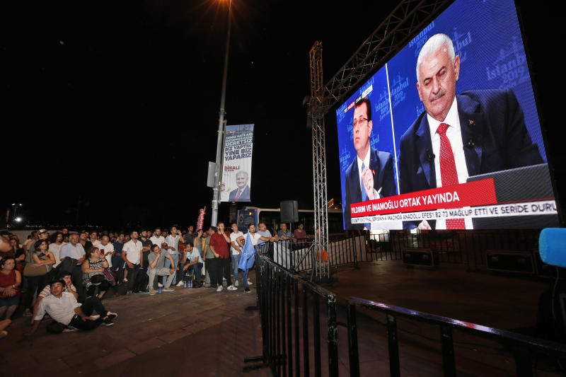 People watch a live broadcast of a televised debate between Istanbul's mayoral candidate Binali Yildirim, right, of Turkey's ruling Justice and Development Party, or AKP, and Ekrem Imamoglu, centre, candidate of the secular opposition Republican People's Party, or CHP, ahead of June 23 re-run of Istanbul elections, Sunday, June 16, 2019. Televised election debates are uncommon in Turkey. The last one, between AKP leader Recep Tayyip Erdogan and the then-leader of the CHP, took place before a 2002. The AKP has been in power since. (AP Photo/Emrah Gurel)