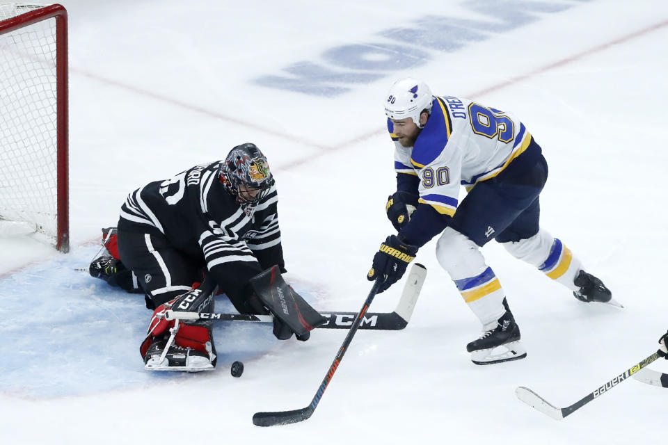 Chicago Blackhawks goaltender Corey Crawford, left, makes a save on a shot by St. Louis Blues' Ryan O'Reilly during the second period of an NHL hockey game Monday, Dec. 2, 2019, in Chicago. (AP Photo/Charles Rex Arbogast)