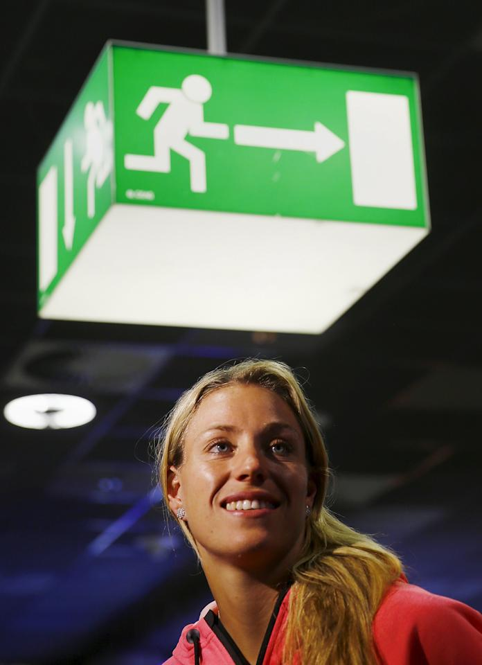 Australian Open winner Angelique Kerber reacts to the applause of members of the media and supporters after her arrival at the airport in Frankfurt, Germany