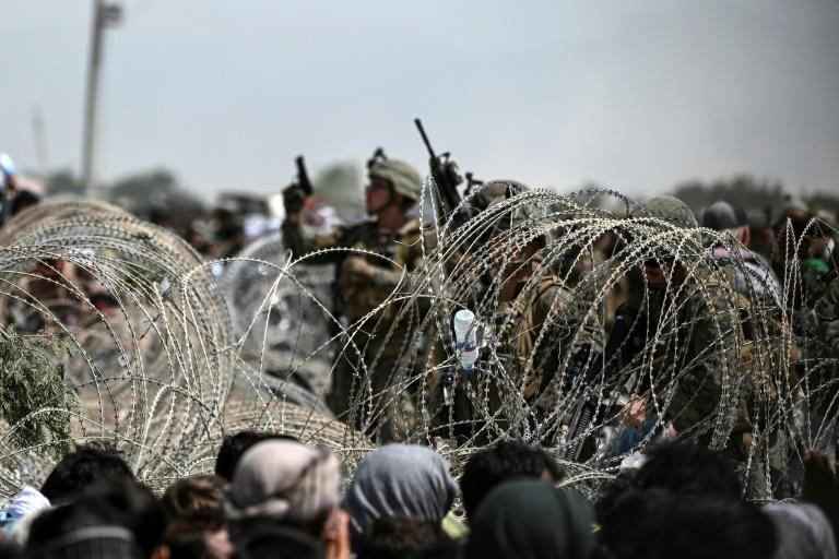 A US soldier shoots in the air with his pistol while standing guard behind barbed wire as Afghans sit on a roadside near the military part of the airport in Kabul