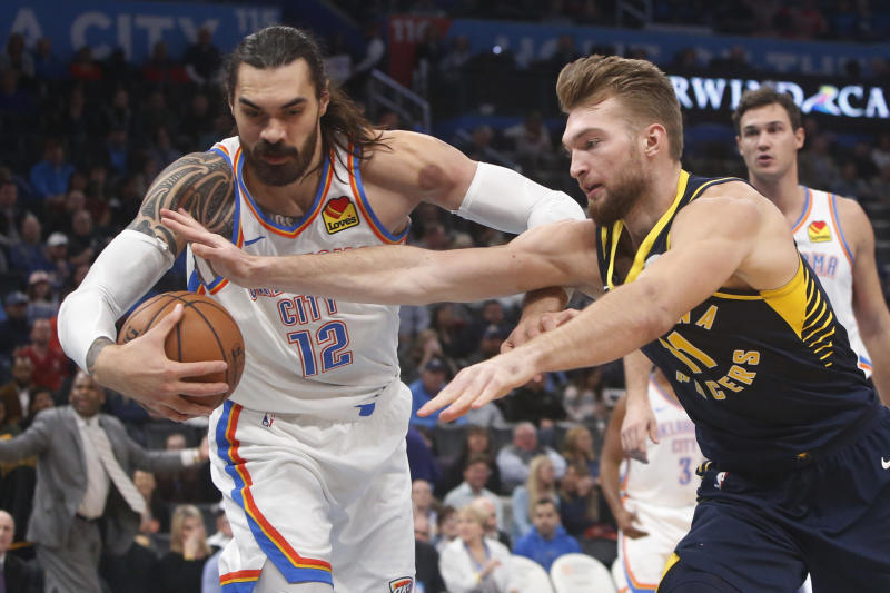 Indiana Pacers forward Domantas Sabonis (11) reaches for the ball held by Oklahoma City Thunder center Steven Adams (12) during the first half of an NBA basketball game Wednesday, Dec. 4, 2019, in Oklahoma City. (AP Photo/Sue Ogrocki)