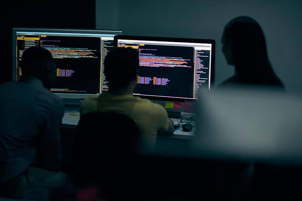 Shot of a group of young businesspeople working on a computer network during a late night at work