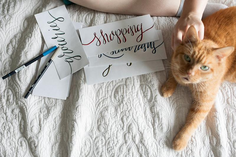 A woman sits on her bed with her cat and envelopes for her cash envelop budgeting system