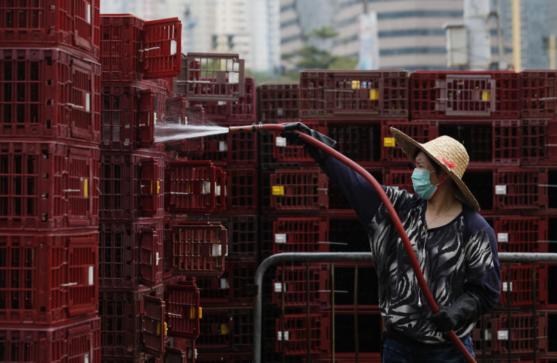 A worker cleans empty cages used for transporting chickens, to prevent an outbreak of H7N9 infections at a wholesale poultry market in Hong Kong Monday, April 8, 2013. The World Health Organization is talking with the Chinese government about sending international experts to China to help investigate a new bird flu strain that has sickened at least 21 people, killing six of them. (AP Photo/Kin Cheung)