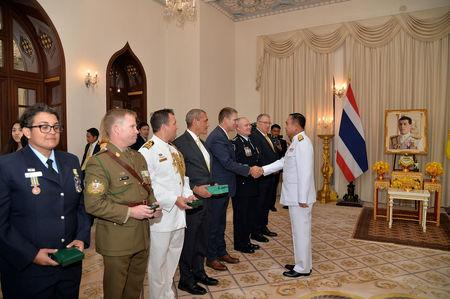 Richard Harris, Australian member of the Thai cave rescue team shakes hands with Thailand's Prime Minister Prayuth Chan-ocha, next to Craig Challen after receiving the Member of the Most Admirable Order of the Direkgunabhorn award at the Government House in Bangkok, Thailand, April 19, 2019. Thailand Government House/Handout via REUTERS