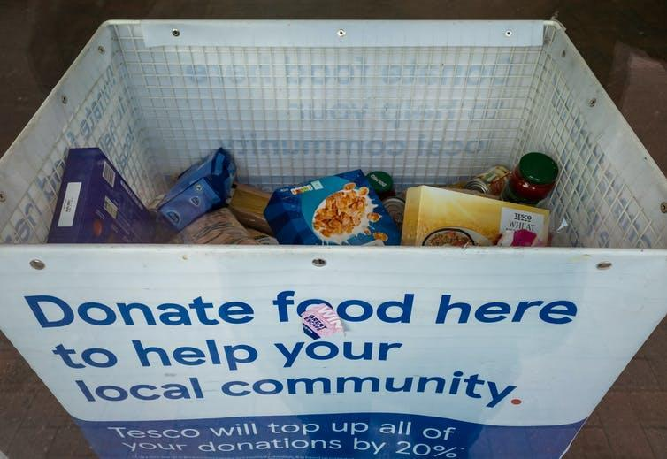 A food donation bin reading 'Donate food here to help your local community.'