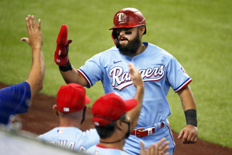 Texas Rangers' Rougned Odor is greeted at the dugout after scoring on an RBI-single by Elvis Andrus in the fourth inning of a baseball game against the Los Angeles Angels in Arlington, Texas, Sunday, Aug. 9, 2020. (AP Photo/Ray Carlin)