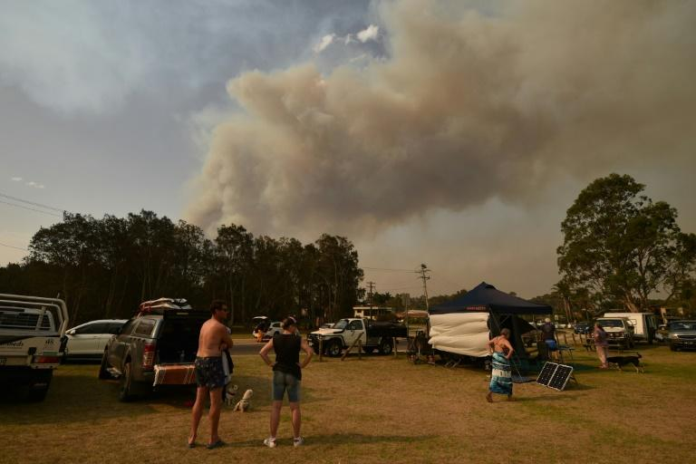 Many people have taken refuge in spots where there is minimal amount of combustible tree cover (AFP Photo/PETER PARKS)