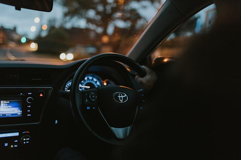 Hayward Heaths, England - October 27th, 2018: Detail of Toyota Auris car steering wheel being driven by young man with the hand on the steering wheel, with night, at right-hand position.