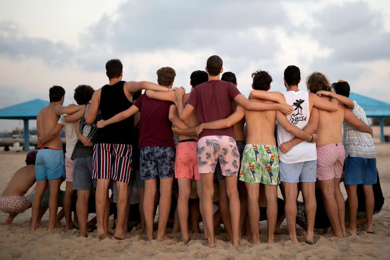 FILE PHOTO: Youths wearing bathing suits, huddle together for a picture as they visit Zikim beach, amid the coronavirus disease (COVID-19) outbreak, in southern Israel