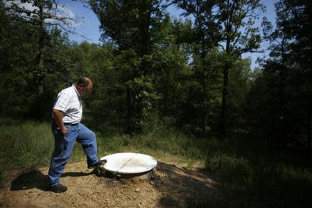 Arkansas Geological Society Geohazards Supervisor stands over a vault which houses a seismometer in Greenbrier, Arkansas