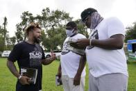 """Phillip Agnew, left, a leader of Black Men Build, speaks to Derrick Williams, right, and Davion Frazier at a """"Free the Vote"""" rally to the polls, Saturday, Oct. 24, 2020, in Miami. Get out the vote efforts targeting Black men aren't just about persuading them to choose former Vice President Joe Biden over incumbent Donald Trump. """"We are not choosing a champion, we are choosing an opponent,"""" says activist Agnew. (AP Photo/Marta Lavandier)"""