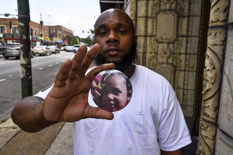 Nathan Wallace stands outside of his home holding a button showing his daughter, Natalia Wallace, 7, who was killed on the west side of Chicago last month. Source: AP