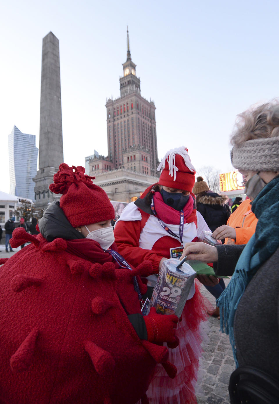 A child in a red costume collects money for Poland's most popular nationwide fundraiser for health purposes, the Great Orchestra of Christmas Charity, that was postponed by two weeks due to the pandemic, in downtown Warsaw, Poland, on Sunday, Jan. 31, 2021. Anti-government protesters angry about a near-total abortion ban suspended their marches for the weekend to show solidarity and ensure that they didn't steal the spotlight from the event. (AP Photo/Czarek Sokolowski)