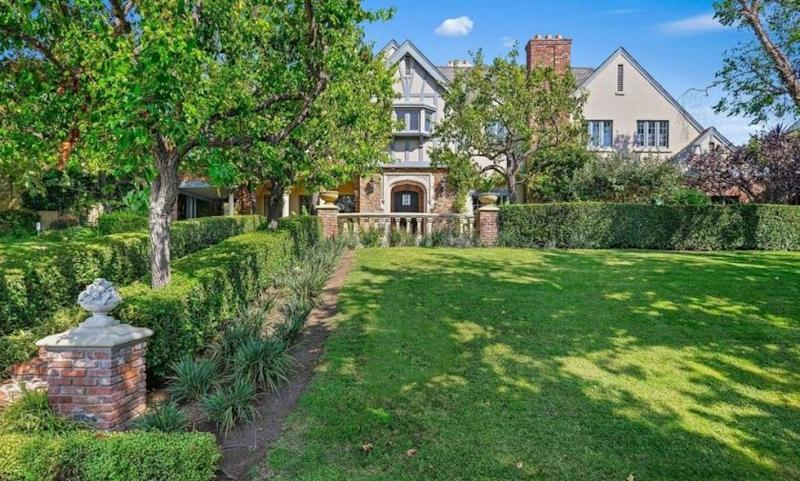 A Tudor-style home sits before an expanse of grassy lawn.