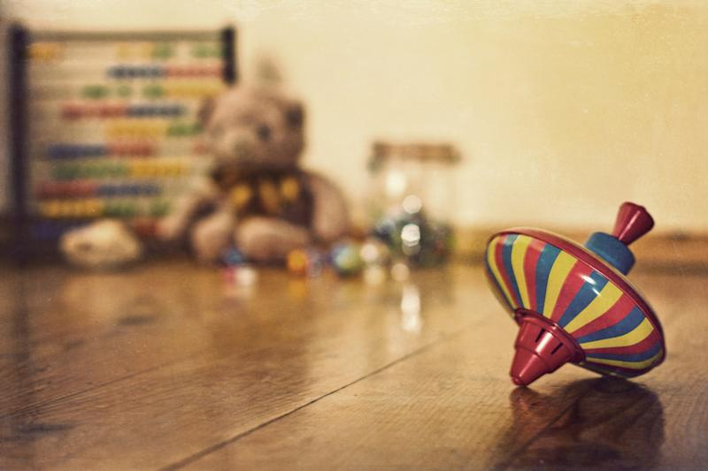 An old fashioned tin spinning top in the foreground with a collection of old fashioned toys in the background including an abacus, teddy bear and marbles.