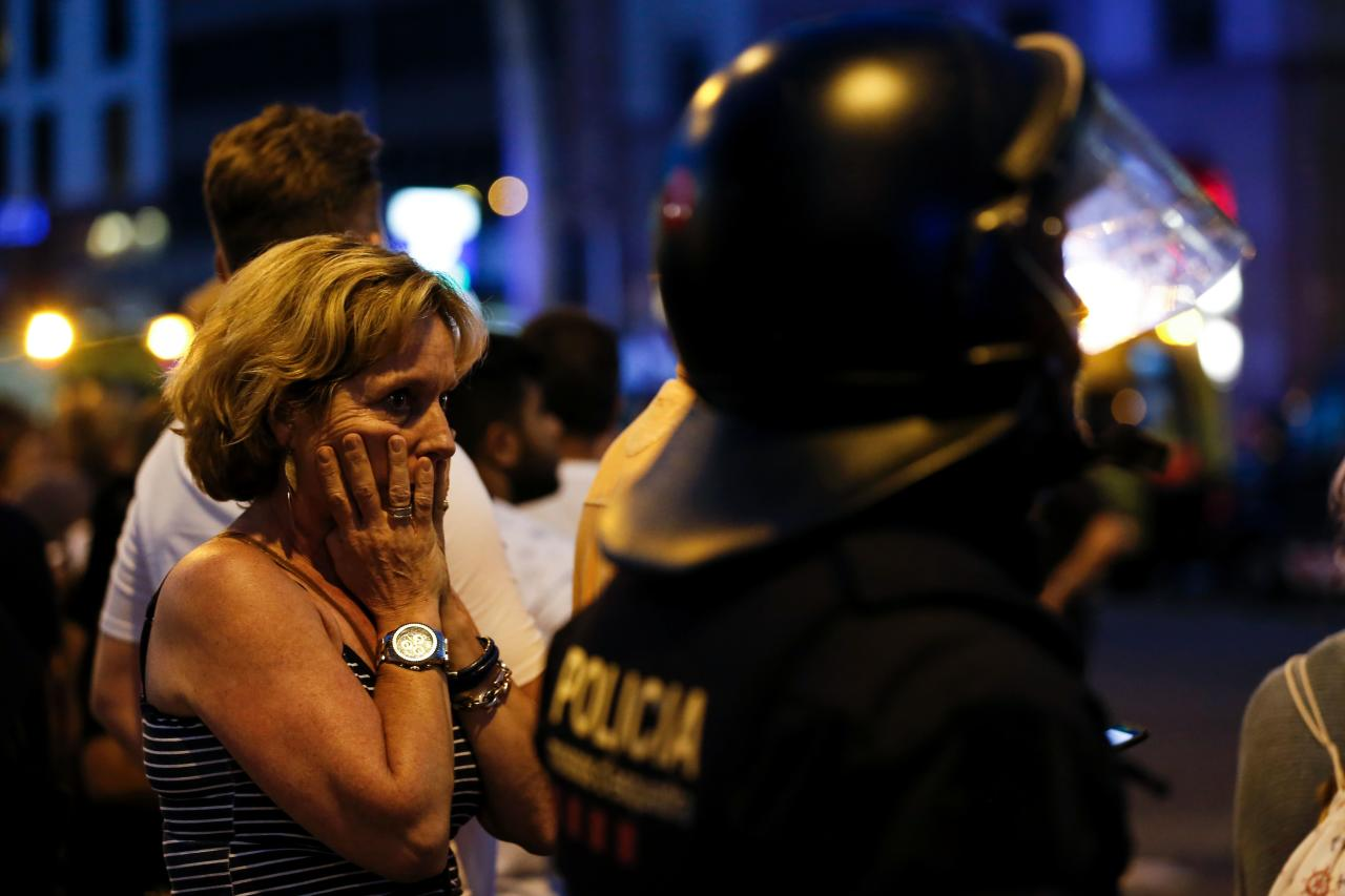 <p>A woman gestures as she is escorted out by Spanish policemen outside a cordoned off area after a van ploughed into the crowd in Barcelona on Aug. 17, 2017. (Pau Barrena/AFP/Getty Images) </p>
