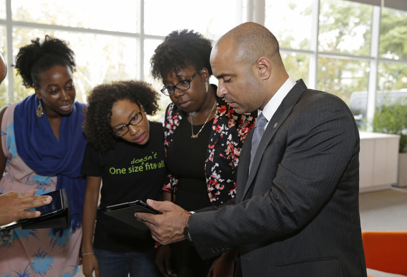 Haiti's Prime Minister Laurent Lamothe, visits with Google employees of Haitian descent from left, Nancy Douyon, Dori Alexandre, and Sheryl Montour during a tour at the Google headquarters complex Wednesday, Nov. 20, 2013, in Mountain View, Calif. From Google to Facebook to Apple, Lamothe plans to spend Wednesday on a whirlwind tour through Silicon Valley's most elite tech campuses, hoping to convince some of the world's wealthiest and most successful corporate executives to share support and innovation with the poorest country in the Americas. (AP Photo/Eric Risberg)