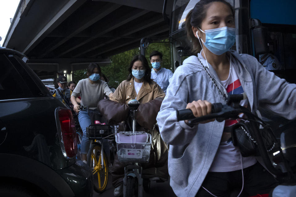 People wearing face masks to protect against COVID-19 make their way through traffic at an intersection in the central business district in Beijing, Thursday, Sept. 16, 2021. China on Thursday reported several dozen additional locally-transmitted cases of coronavirus as it works to contain an outbreak in the eastern province of Fujian. (AP Photo/Mark Schiefelbein)