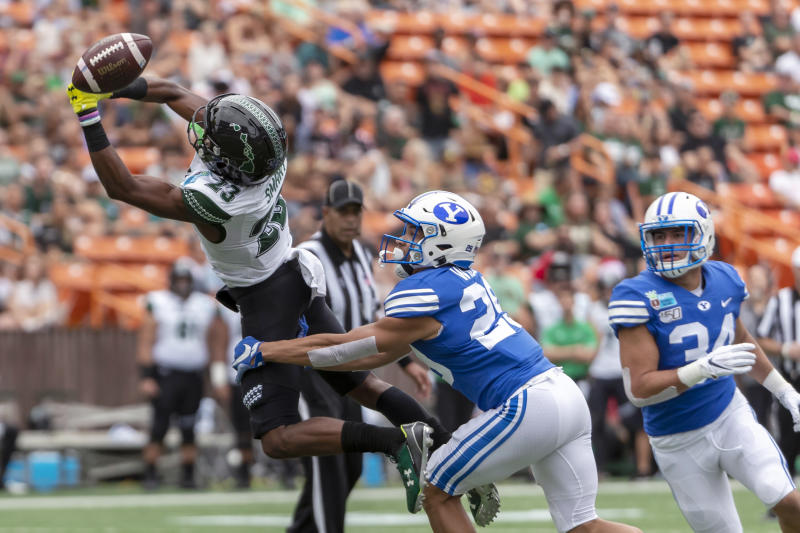 The football is just out of reach of Hawaii wide receiver Jared Smart (23) as BYU defensive back Shamon Willis (29) and linebacker Kavika Fonua (34) defend during the first half of the Hawaii Bowl NCAA college football game Tuesday, Dec. 24, 2019, in Honolulu. (AP Photo/Eugene Tanner)