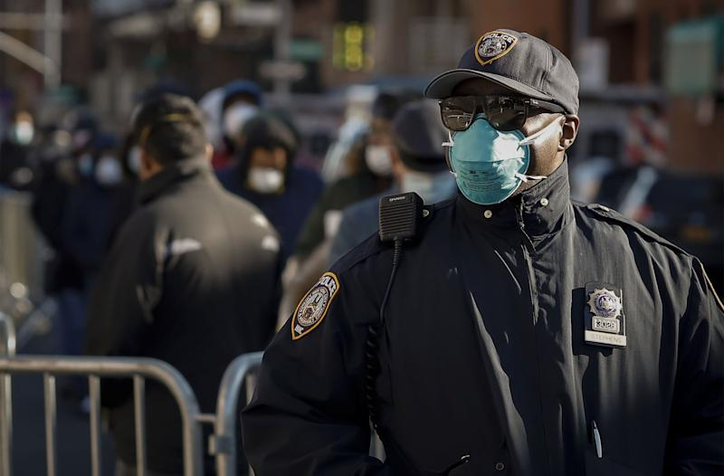 A New York City police officer wears protective gear while monitoring people waiting in line to be tested for the coronavirus outside Elmhurst Hospital in Queens on March 26. (Stefan Jeremiah / Reuters)