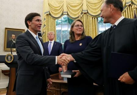 U.S. President Donald Trump looks on as Mark Esper shakes hands with Associate Justice Samuel Alito after Esper was sworn in as the new Secretary of Defense while Esper's wife Leah Esper stands nearby in the Oval Office of the White House