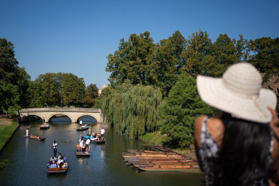 People make the most of the hot weather as they enjoy punt tours along the River Cam in Cambridge (Joe Giddens/PA) (PA Wire)