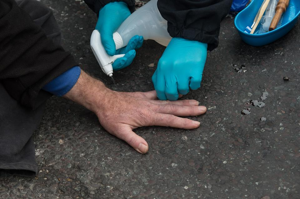 ESSEX, ENGLAND - OCTOBER 13: Police spray solvent onto a hand that is superglued to the road as they arrest activists from Insulate Britain block a junction near the Dartford Crossing on October 13, 2021 in Thurrock, England.(Photo by Guy Smallman/Getty Images)