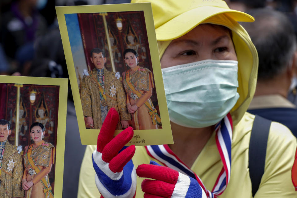 A supporter of the Thai monarchy displays images of King Maha Vajiralongkorn and Queen Suthida during a gathering outside German Embassy in central Bangkok, Thailand Monday, Oct. 26, 2020. The royalists gathered to defend pro-democracy protesters' contention that King Maha Vajiralongkorn spends much of his time in Germany conducting Thai political activities. German government officials have recently expressed concern over political activities the king might be conducting on the Germany's soil. (AP Photo/Gemunu Amarasinghe)