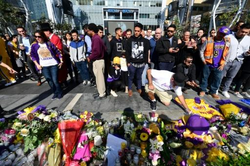 Fans place flowers, candles and other mementos to honor Kobe Bryant at LA LIVE plaza in Los Angeles