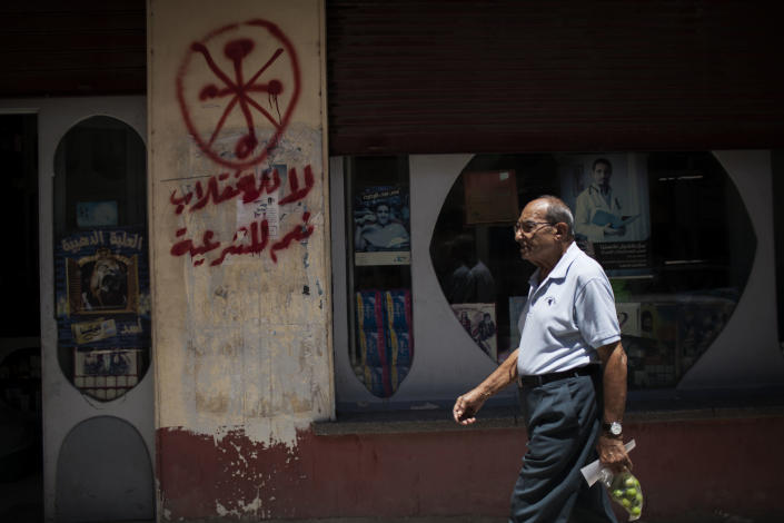 """An Egyptian man walks in front of a pharmacy marked with anti-Coptic and anti-coup graffiti in Assiut, Upper Egypt, Tuesday, Aug. 6, 2013. Islamists may be on the defensive in Cairo, but in Egypt's deep south they still have much sway and audacity: over the past week, they have stepped up a hate campaign against the area's Christians. Blaming the broader Coptic community for the July 3 coup that removed Islamist President Mohammed Morsi, Islamists have marked Christian homes, stores and churches with crosses and threatening graffiti. Arabic grafitti reads, """"No to the coup and yes to legitimacy."""" (AP Photo/Manu Brabo)"""
