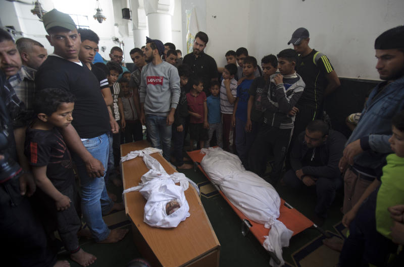 Palestinians stand around the bodies of a four-months-old girl Maria Al-Ghazali, her father Ahmad and mother Iman Al-Ghazali, laid inside a coffin, who were killed in a late Sunday Israeli missile strike during their funeral in town of Beit Lahiya, northern Gaza Strip, Monday, May. 6, 2019. (AP Photo/Abdel Kareem Hana)