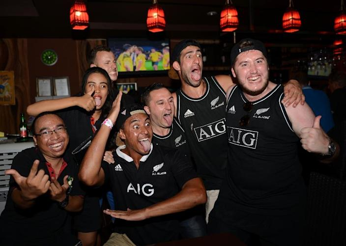 New Zealand supporters in Kuta, on Indonesia's resort island of Bali, celebrate their team's victory over Australia in the final of the 2015 Rugby World Cup, on November 1, 2015 (AFP Photo/Sonny Tumbelaka)