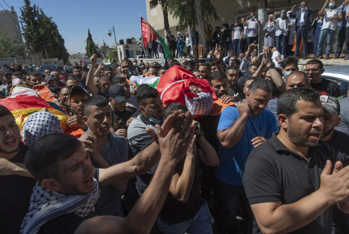 Palestinian mourners carry the bodies of Islam Bernat, 16, left and Adham Kashef, 20, during their funeral in the West Bank city of Ramallah, Wednesday, May 19, 2021. Multiple protesters were killed and more than 140 wounded in clashes with Israeli troops in Ramallah, Bethlehem, Hebron and other cities on Tuesday, according to the Palestinian Health Ministry. The Israeli army said at least a few soldiers were wounded in Ramallah by gunshots to the leg. (AP Photo/Nasser Nasser)