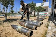 An explosives expert of Hamas lays out unexploded projectiles from the 11-day conflict with Israel last month, at a local police precinct in Khan Yunis in the southern Gaza Strip