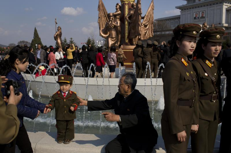 North Korean soldiers and civilians pose for souvenir photos in front of a fountain as they tour the grounds of Kumsusan Palace of the Sun, the mausoleum where the bodies of the late leaders Kim Il Sung and Kim Jong Il lie embalmed, in Pyongyang on Thursday, April 25, 2013. North Korea on Thursday marked the 81st anniversary of the founding of its military, which began as an anti-Japanese militia and now has an estimated 1.2-million troops. (AP Photo/David Guttenfelder)