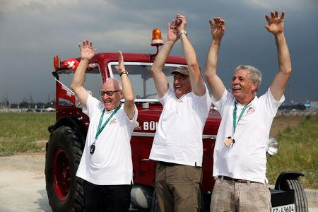 Swiss fans Josef Wyer, Beat Studer and Werner Zimmermann celebrate after driving an old-time tractor from home to Kaliningrad stadium to watch their team playing against Serbia, in Kaliningrad, Russia June 21, 2018. REUTERS/Mariana Bazo