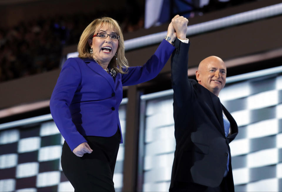 FILE - In this July 27, 2016, file photo, former Rep. Gabby Giffords, D-Ariz, and her husband Astronaut Mark Kelly (ret.), walk off the stage after speaking during the Democratic National Convention in Philadelphia. As a mob laid siege to the U.S. Capitol this week, former Rep. Giffords waited nervously for news about her husband, Kelly, who was barely a month into his job as a newly elected senator from Arizona. A decade earlier it was Kelly enduring the excruciating wait for news about Giffords, who was shot in the head in an attempted assassination that, like the siege, Jan. 6, 2021, shocked the nation and prompted a reckoning about the state of politics and discourse in the U.S. (AP Photo/Carolyn Kaster, File)